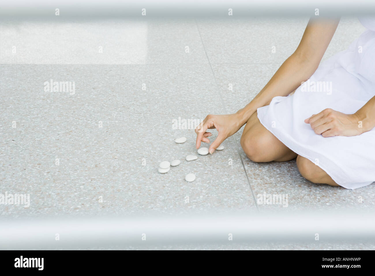 Woman sitting on the ground arranging pebbles, cropped view - Stock Image