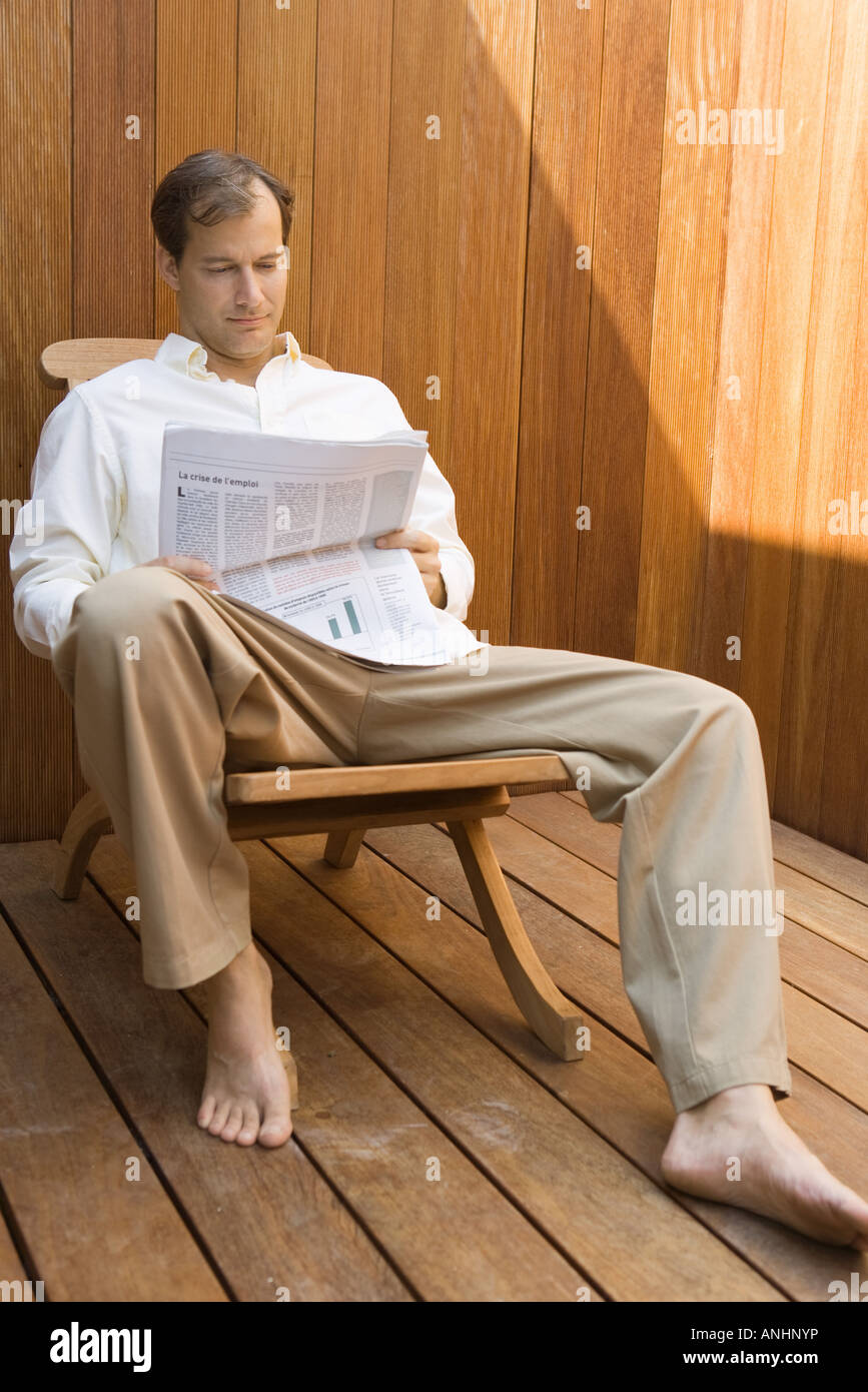 Man Sitting In Lounge Chair Reading Newspaper