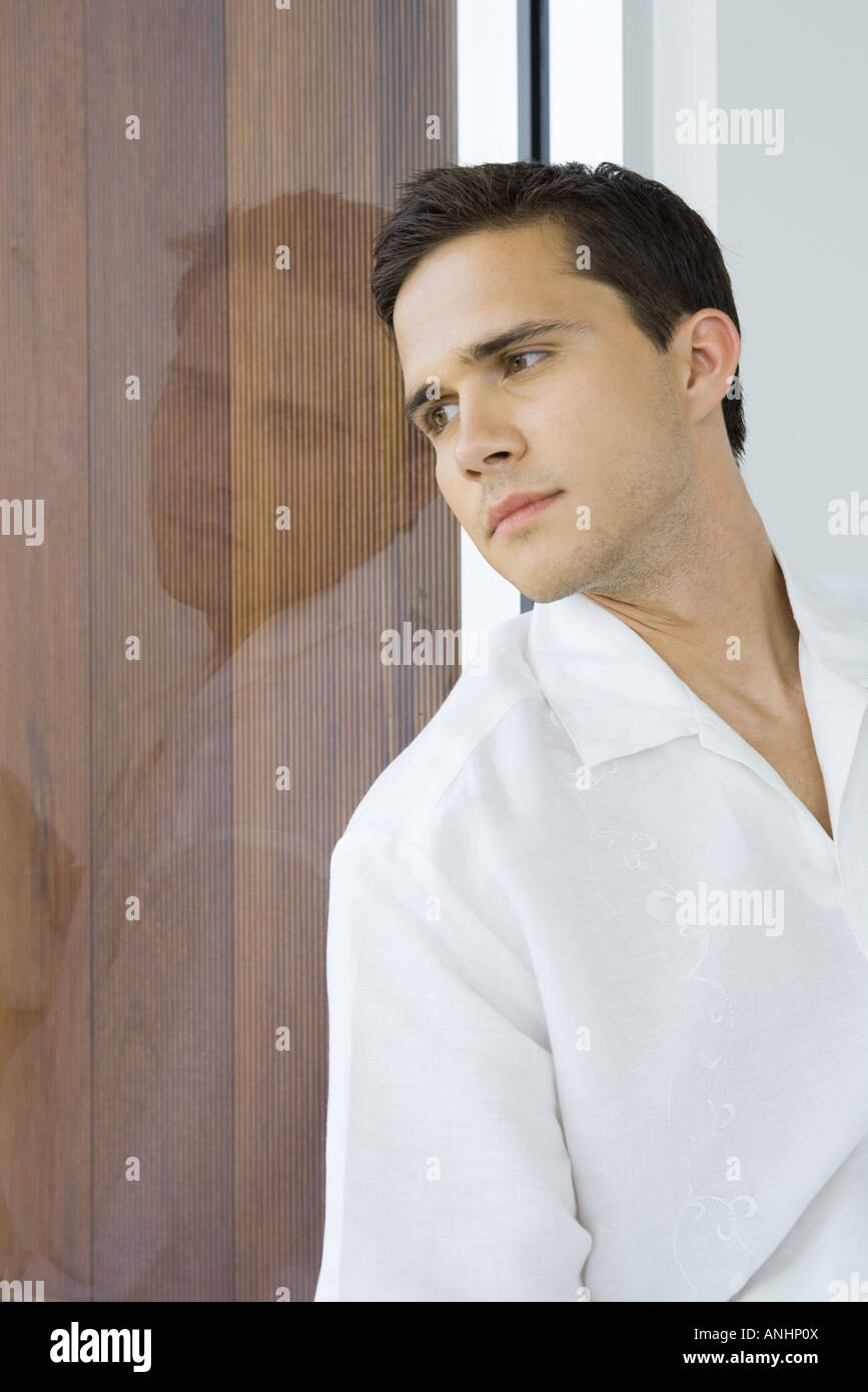 Young man leaning against window, looking out, close-up - Stock Image