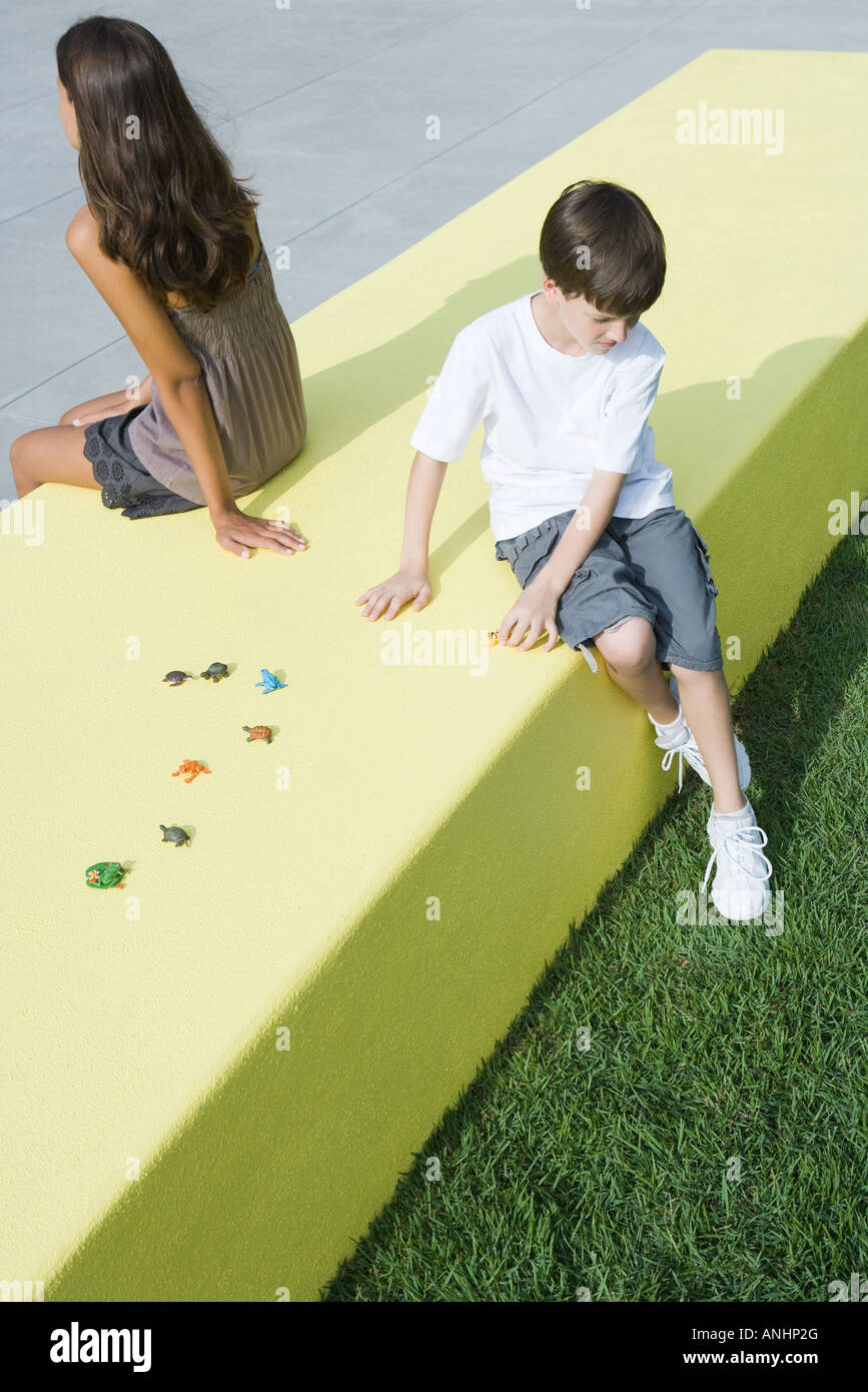 Brother and sister sitting back to back on low wall next to toys, high angle view Stock Photo