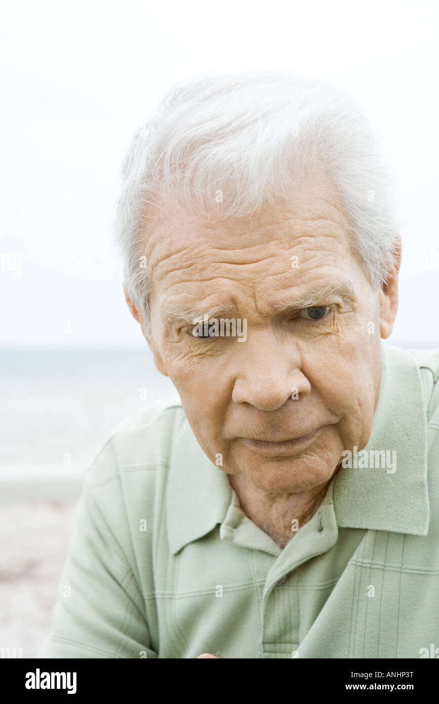 Senior man looking down, furrowing brow, close-up - Stock Image