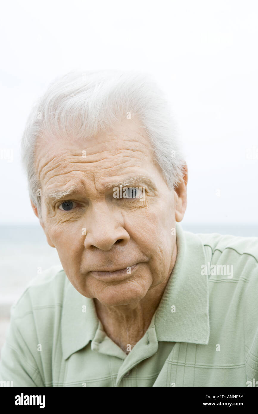 Senior man looking at camera, furrowing brow, portrait - Stock Image