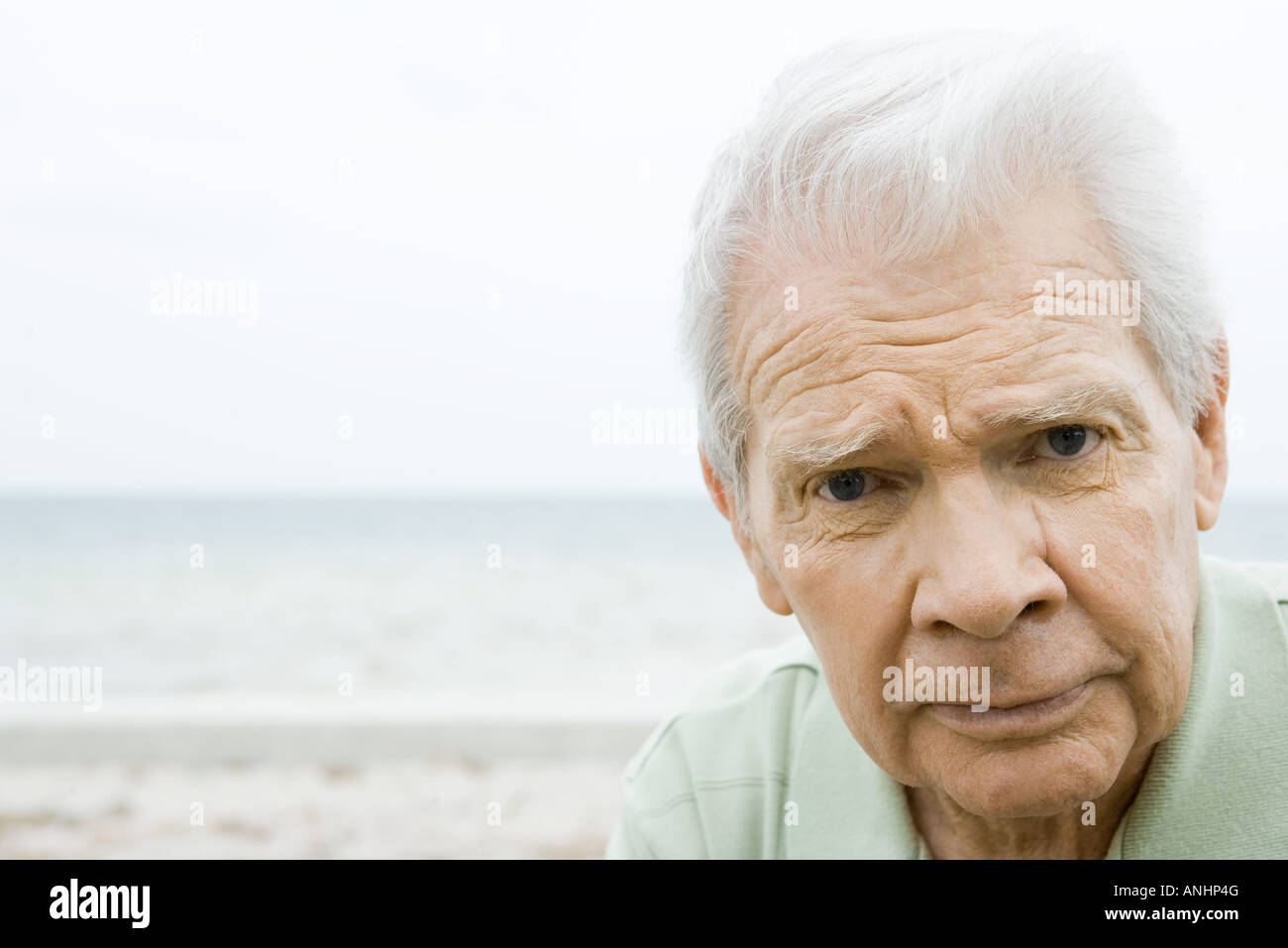 Senior man looking at camera, furrowing brow, close-up - Stock Image