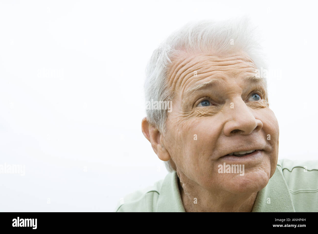 Senior man looking up, smiling, portrait - Stock Image