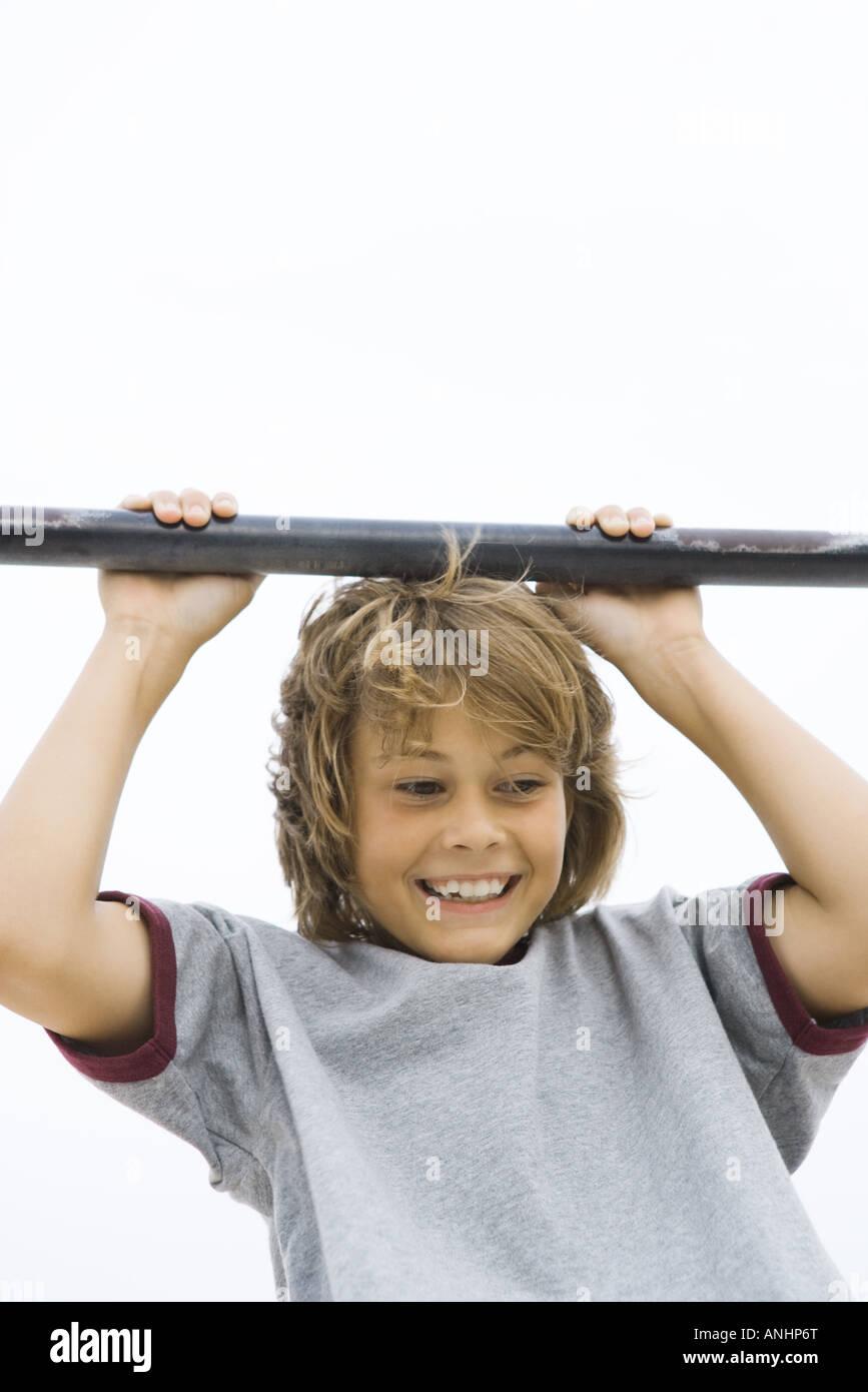 Boy hanging from metal bar, smiling, cropped view - Stock Image