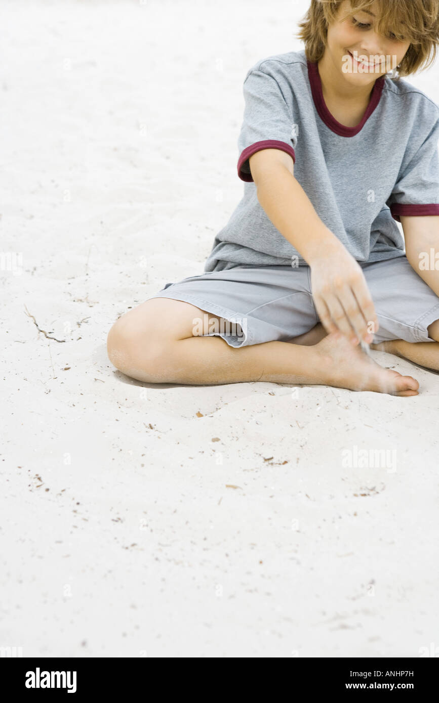 Boy playing in sand, smiling, cropped view - Stock Image
