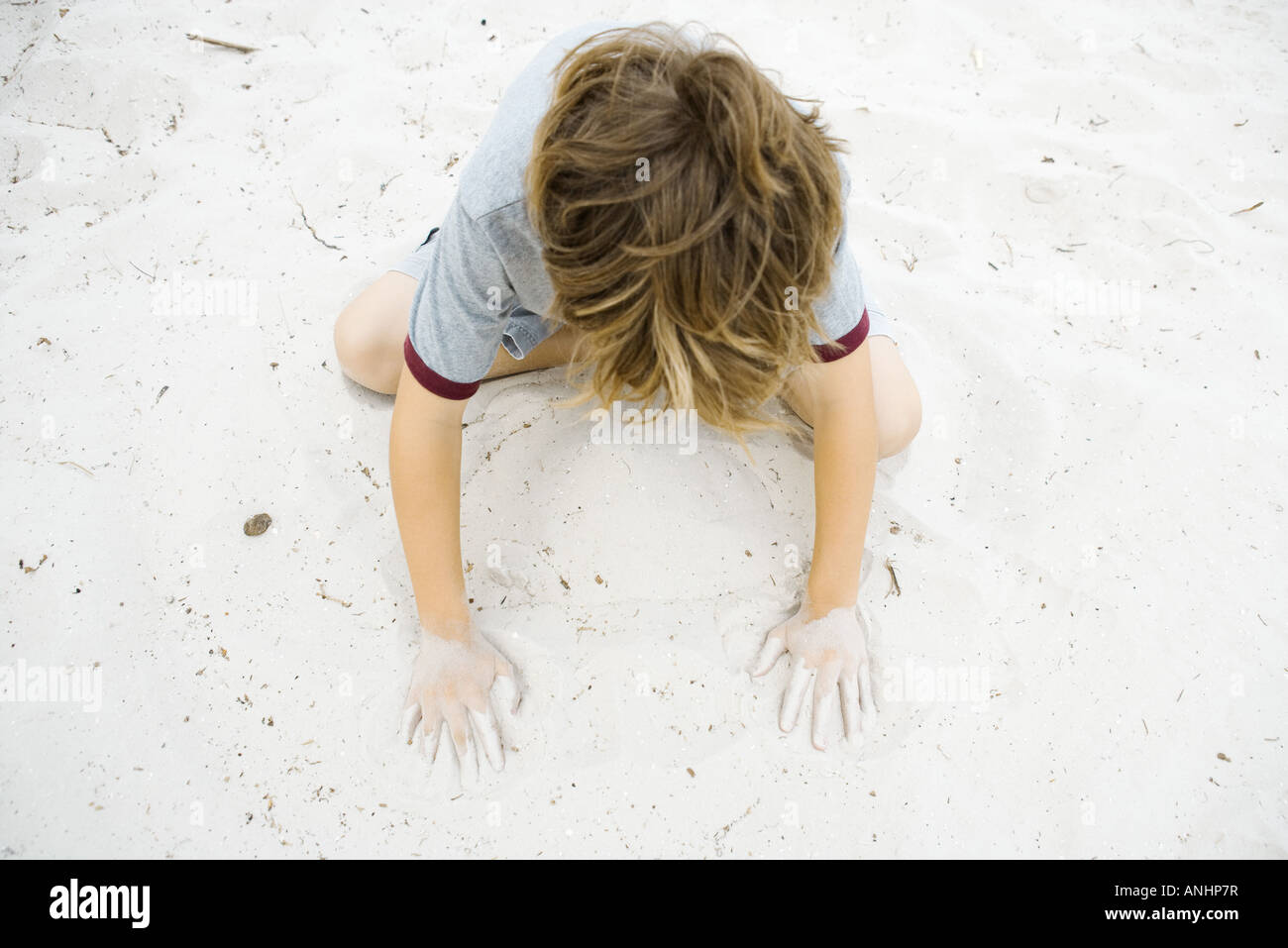 Boy crouching in sand, playing, high angle view - Stock Image