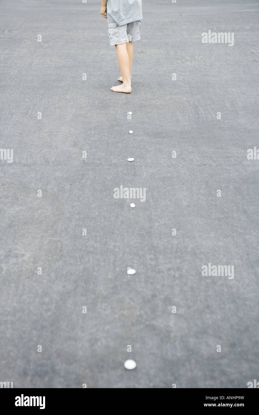 Child walking along line of pebbles, cropped rear view - Stock Image