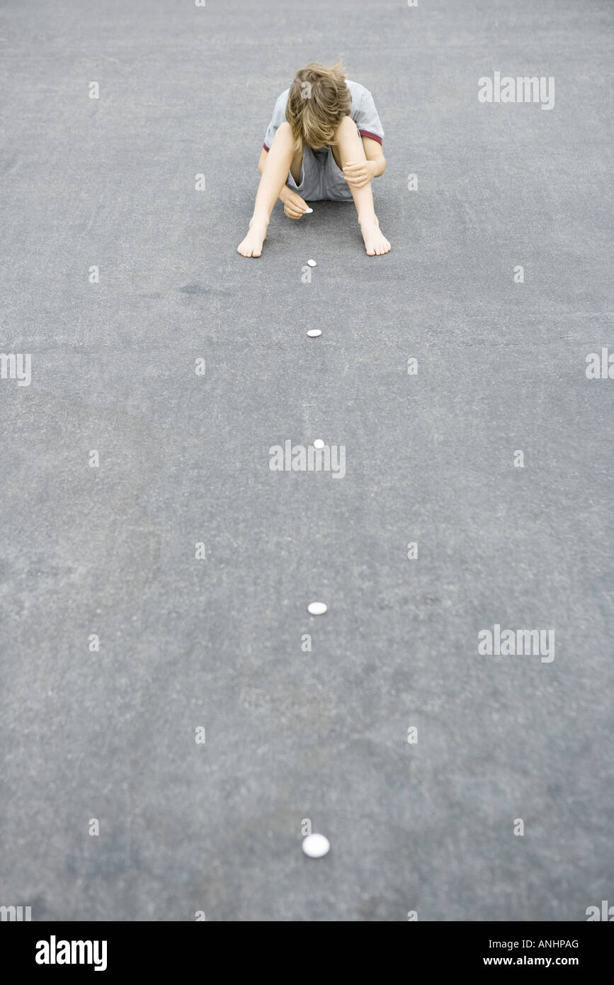 Boy sitting on the ground arranging line of pebbles, high angle view - Stock Image