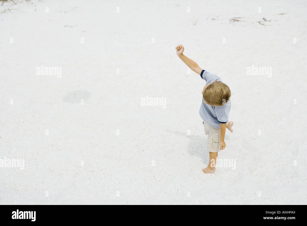 Young boy walking on the beach with one arm raised, high angle view - Stock Image