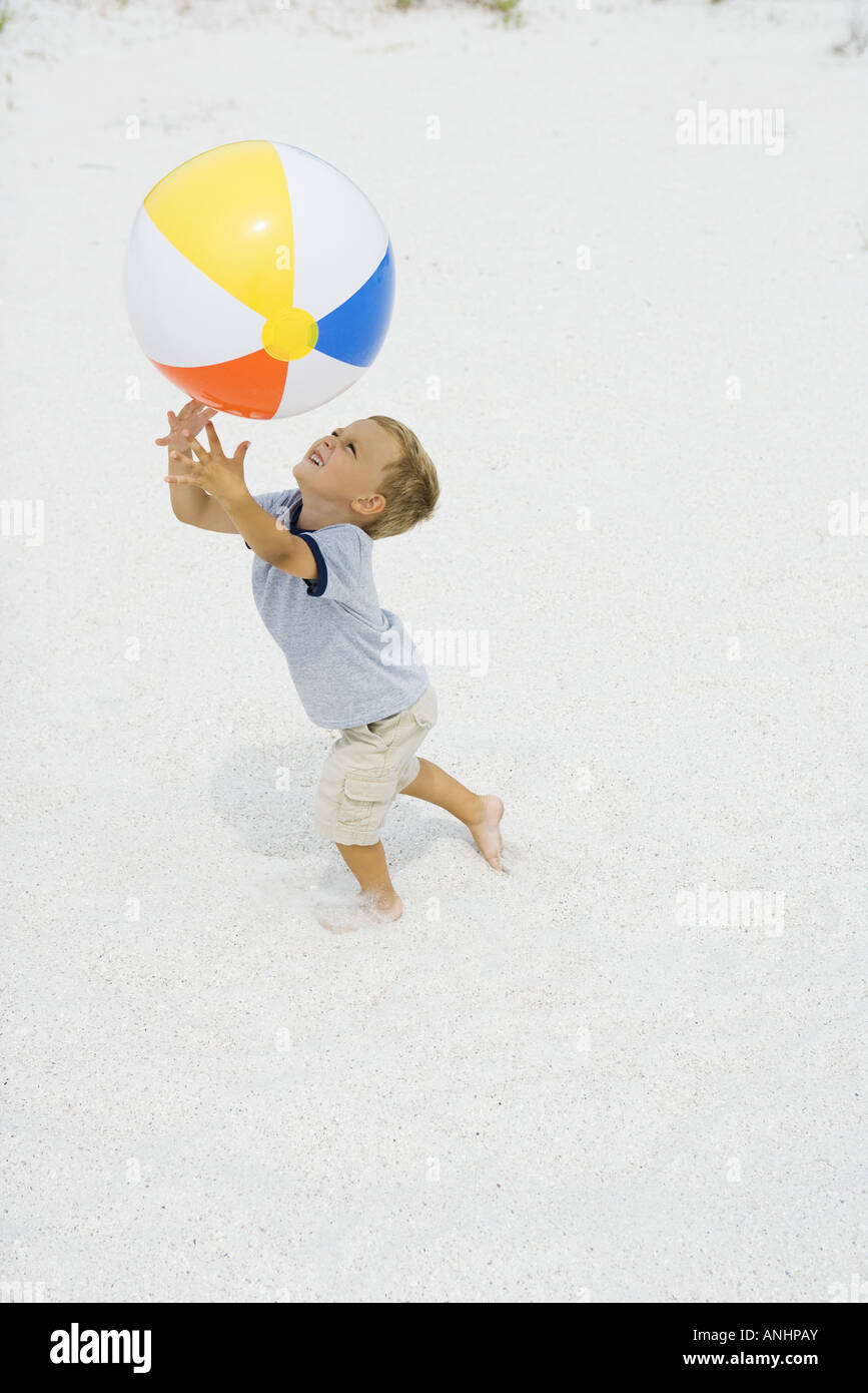 Young Boy Catching Beach Ball Arms Raised Side View Stock
