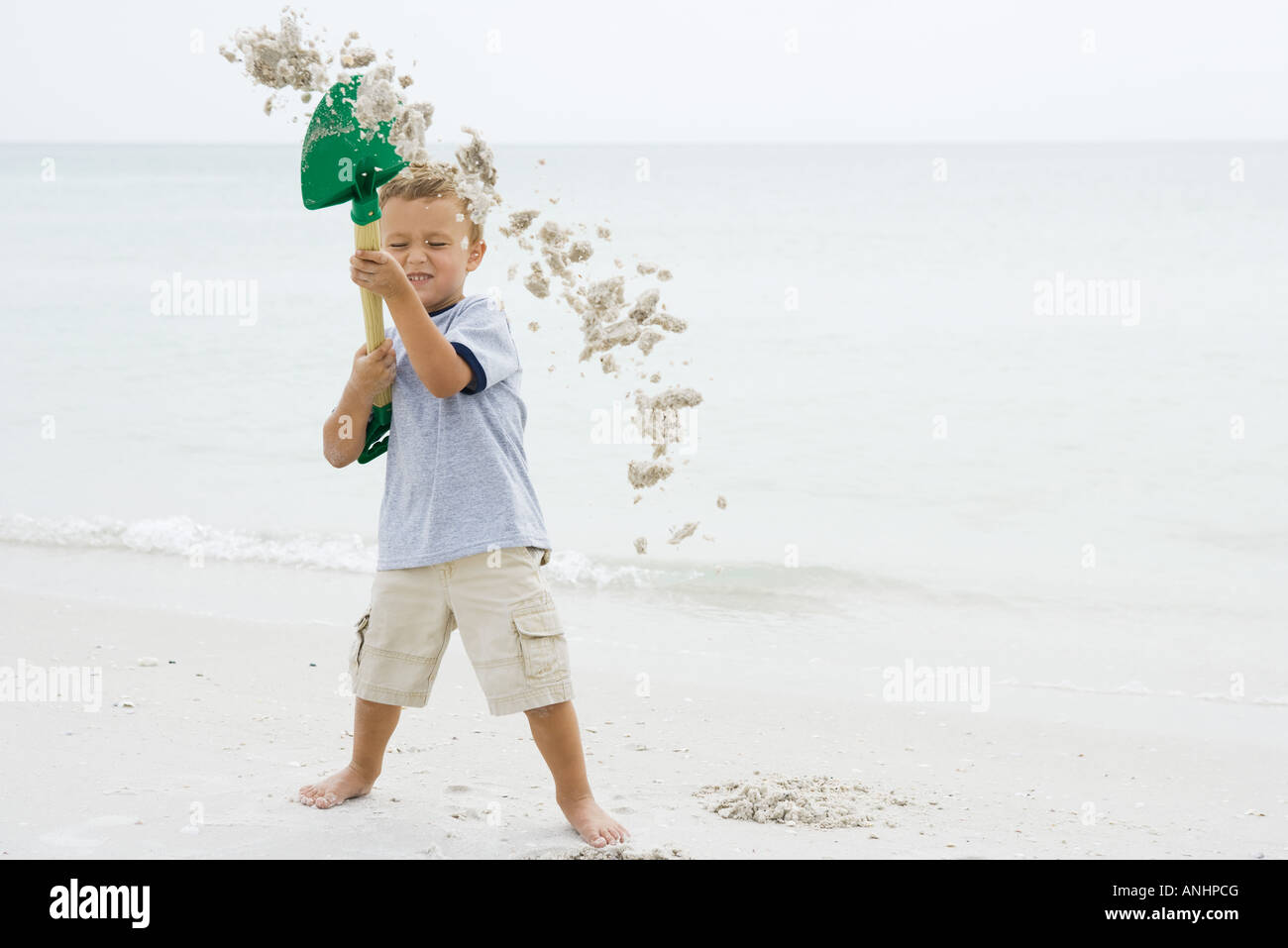 Young boy at the beach holding up shovel, throwing sand, eyes closed - Stock Image