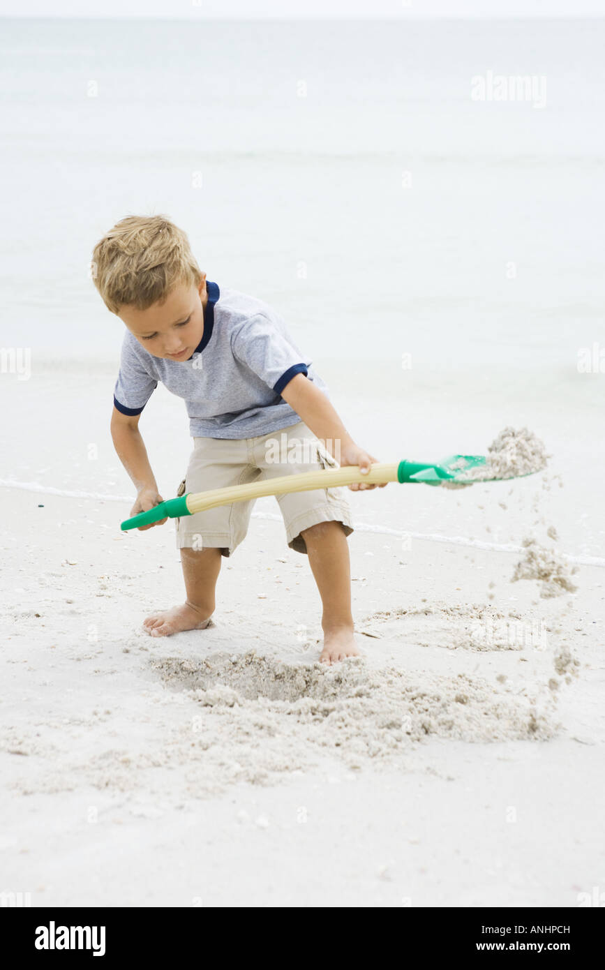 Young boy standing on beach, digging in sand with shovel, looking down - Stock Image