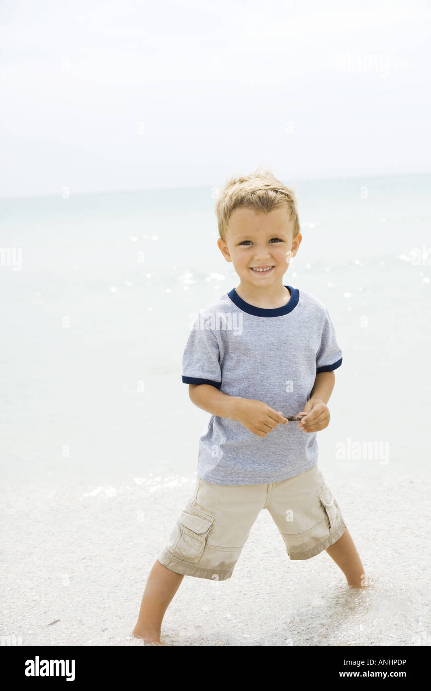 Young boy standing ankle deep in water at the beach, smiling at camera - Stock Image