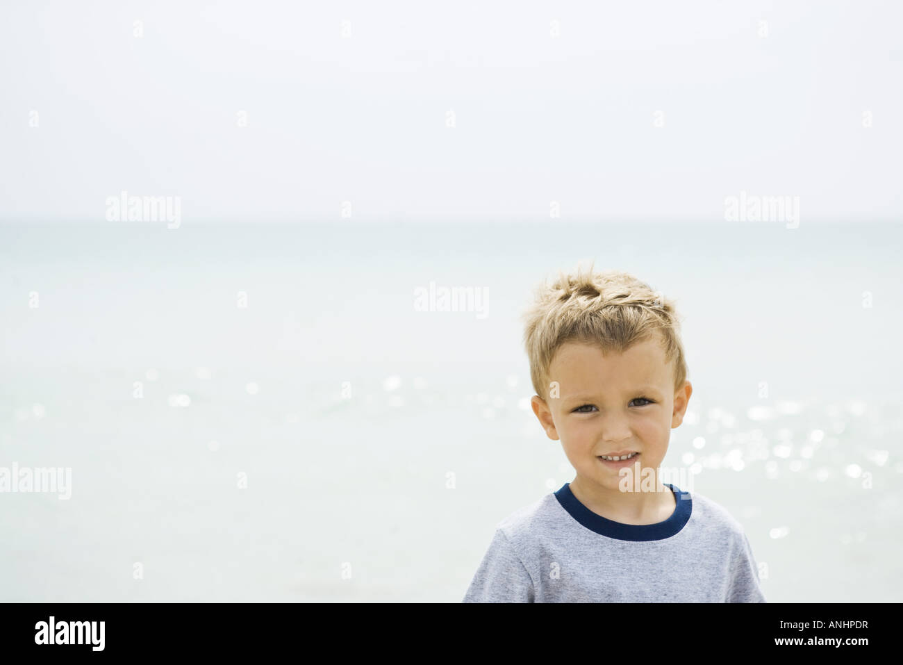 Young boy at the beach, smiling at camera, portrait - Stock Image