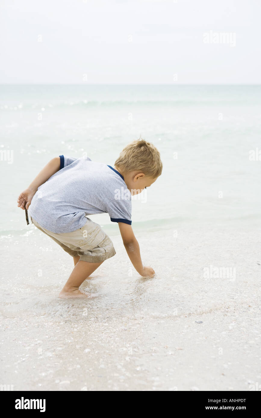 Young boy at the beach, bending over to pick up seashell, side view - Stock Image