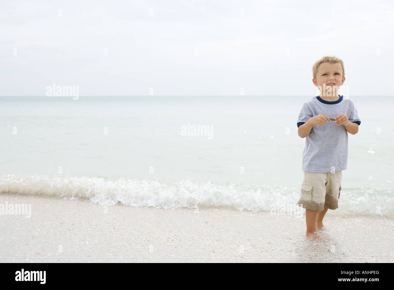 Boy at the beach, standing ankle deep in water, looking up and smiling - Stock Image
