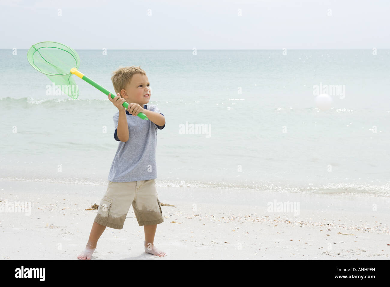 Young boy at the beach, holding up net to catch ball - Stock Image