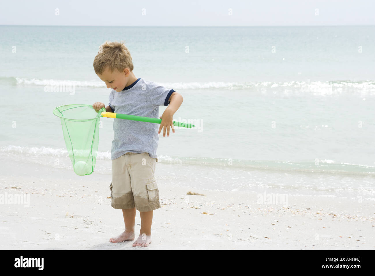 Young boy standing at the beach, holding ball in net, looking down - Stock Image