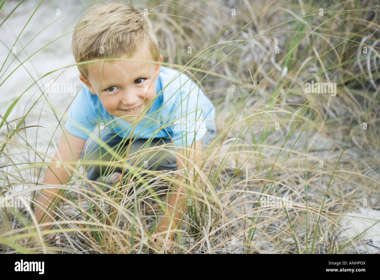 Young boy crouching in tall grass, looking away, smiling - Stock Image
