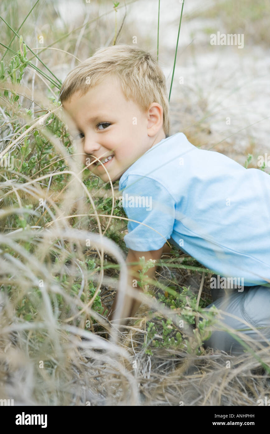 Young boy crouching in tall grass, looking over shoulder at camera Stock Photo
