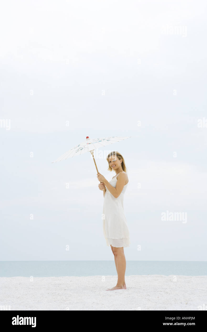 Woman in sundress standing at the beach, holding up parasol, smiling at camera - Stock Image