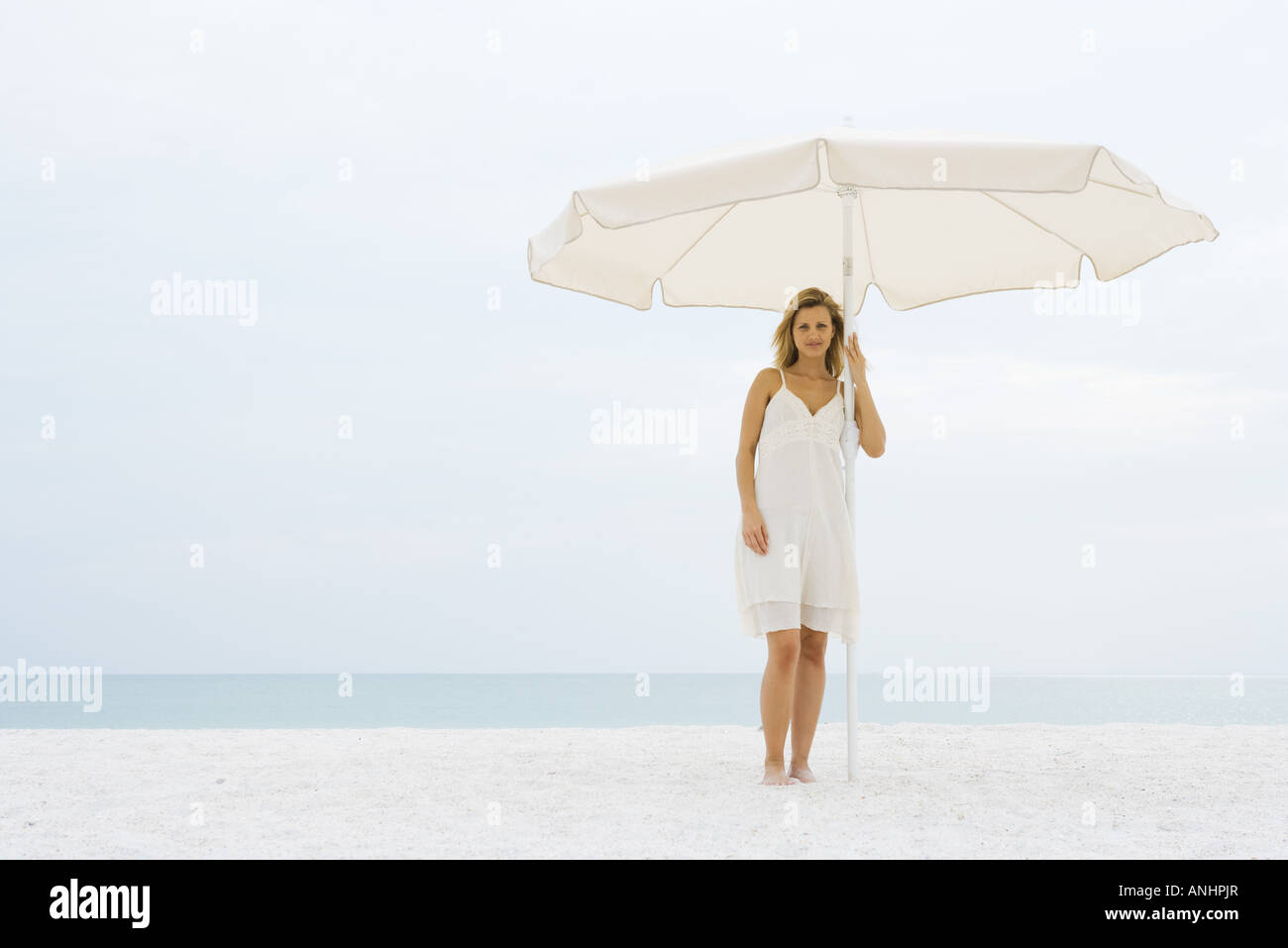 Woman in sundress standing under umbrella at the beach, looking at camera - Stock Image