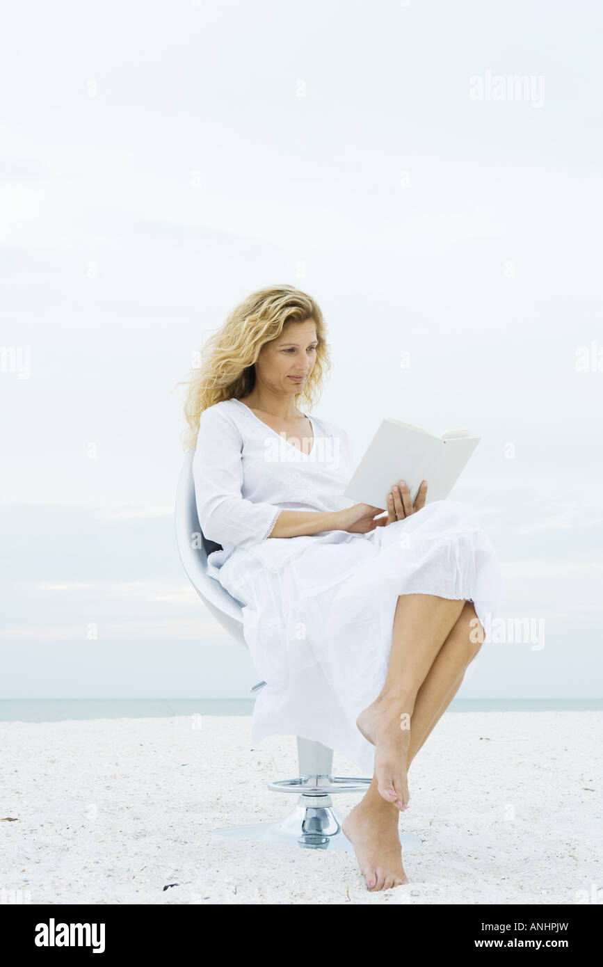 Woman sitting in chair at the beach, reading book - Stock Image