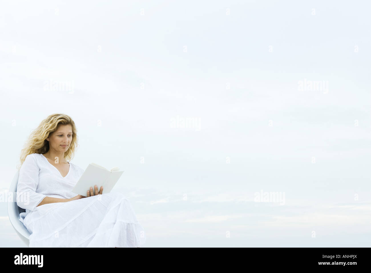 Woman sitting in chair outdoors, reading book - Stock Image