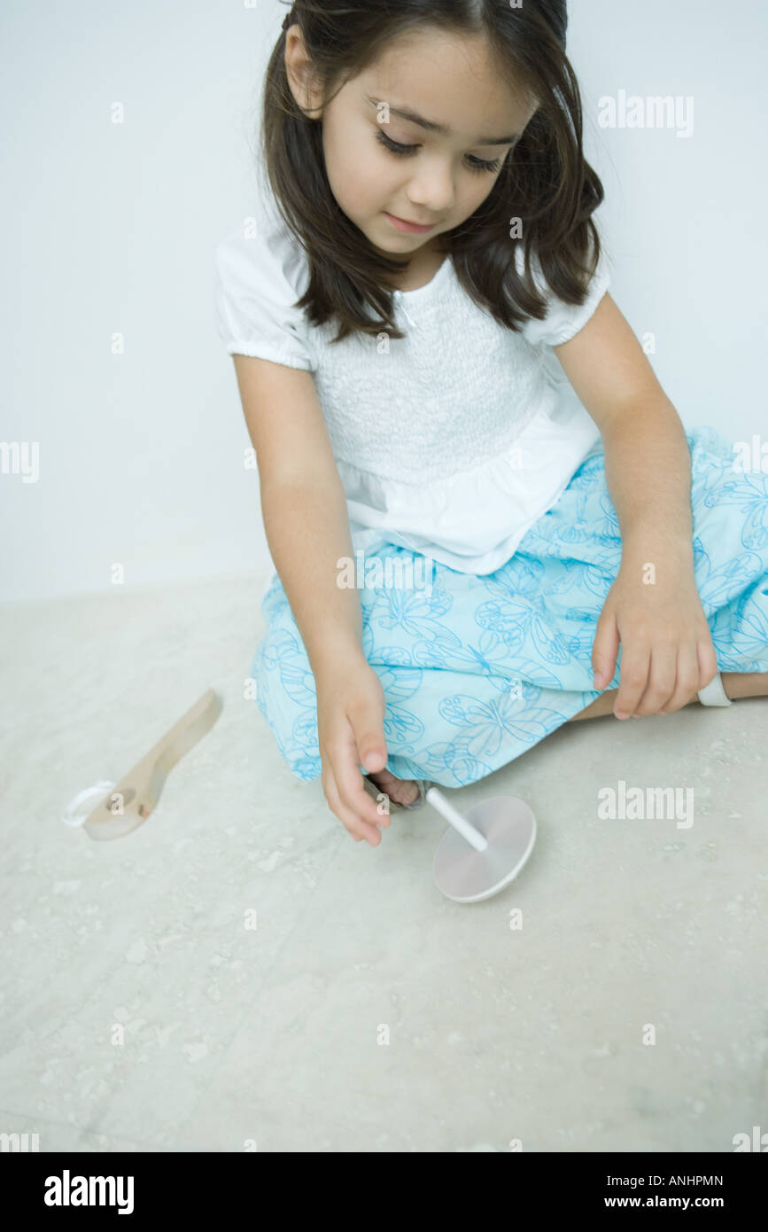 Girl sitting on the ground playing with top, close-up - Stock Image