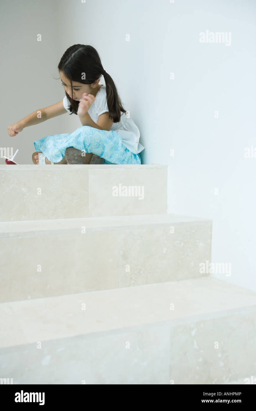 Girl sitting on steps playing with top, low angle view - Stock Image