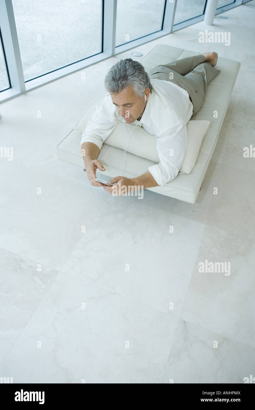 Mature man lying on chaise longue listening to mp3 player, high angle view - Stock Image