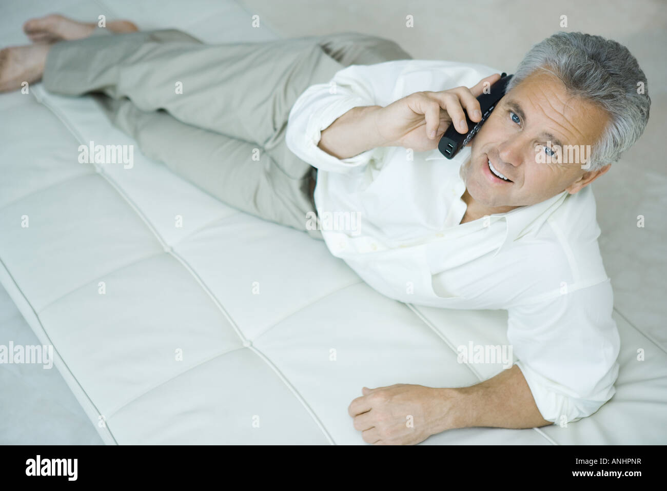 Mature man lying on chaise longue using cordless phone, looking up at camera - Stock Image