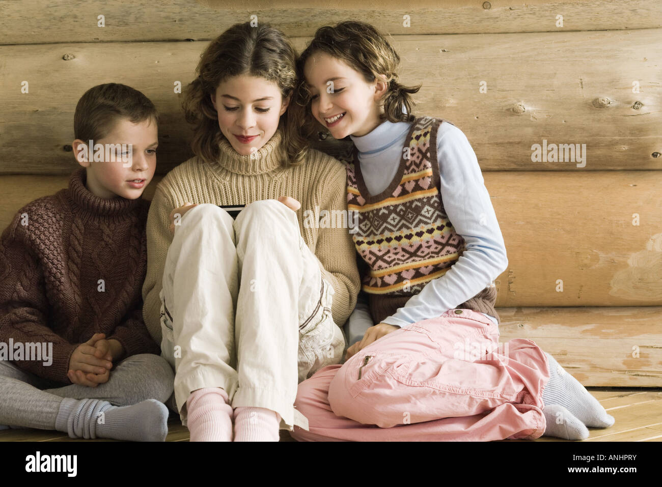 Boy and girl watching teen girl play video game Stock Photo