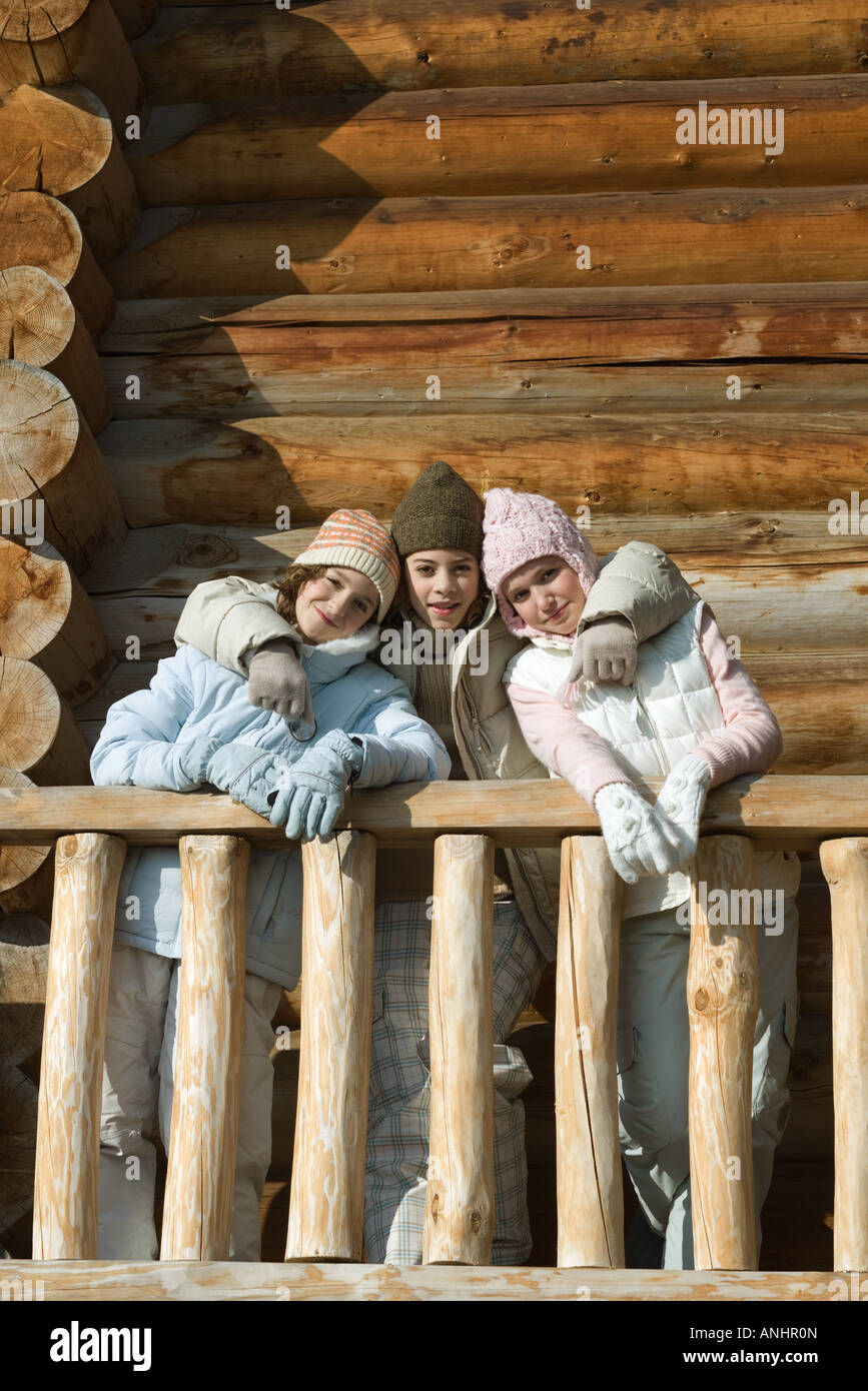 Three preteen or teen girls standing on deck of log cabin, smiling at camera - Stock Image