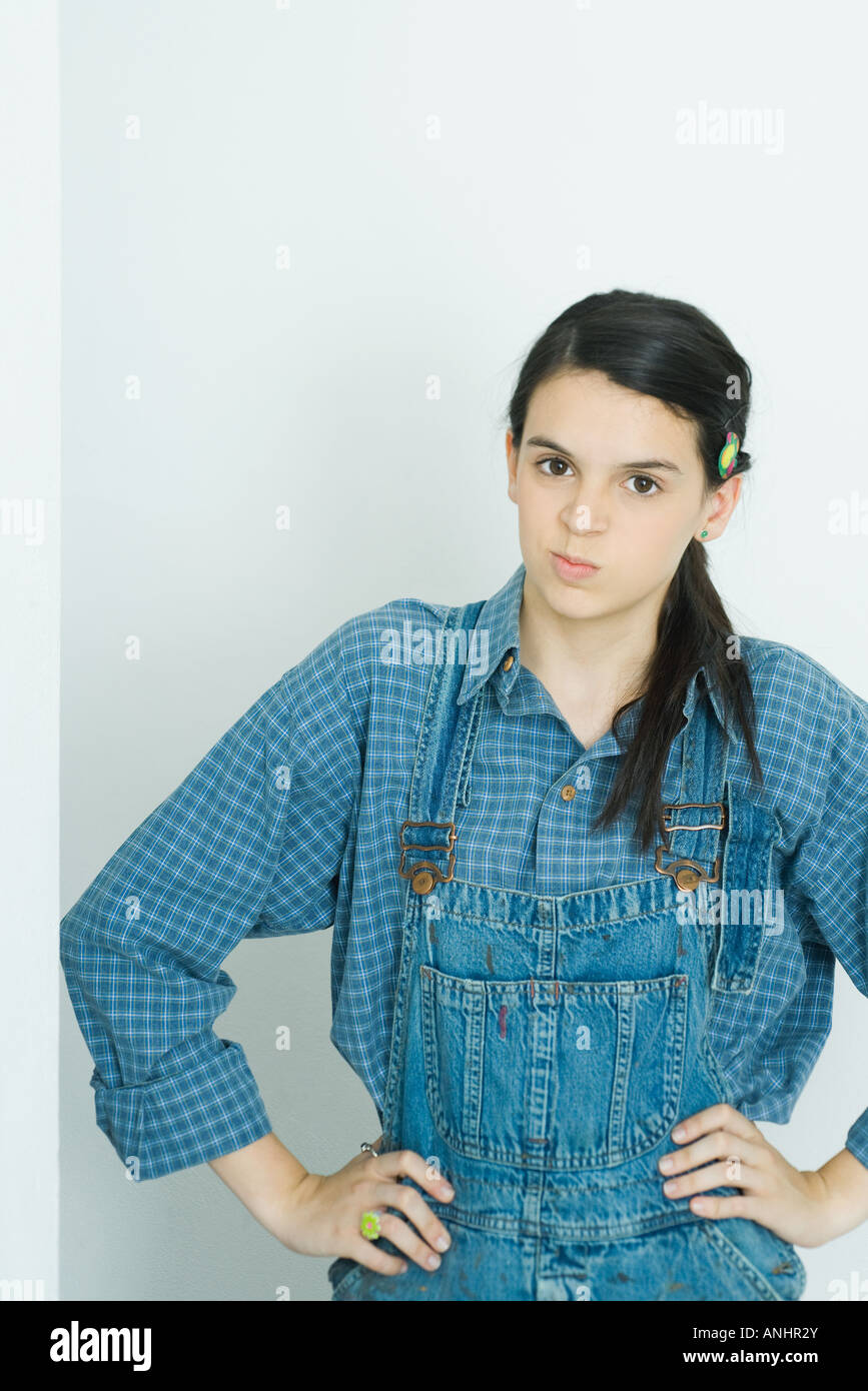 Teenage girl with hands on hips, smirking at camera - Stock Image