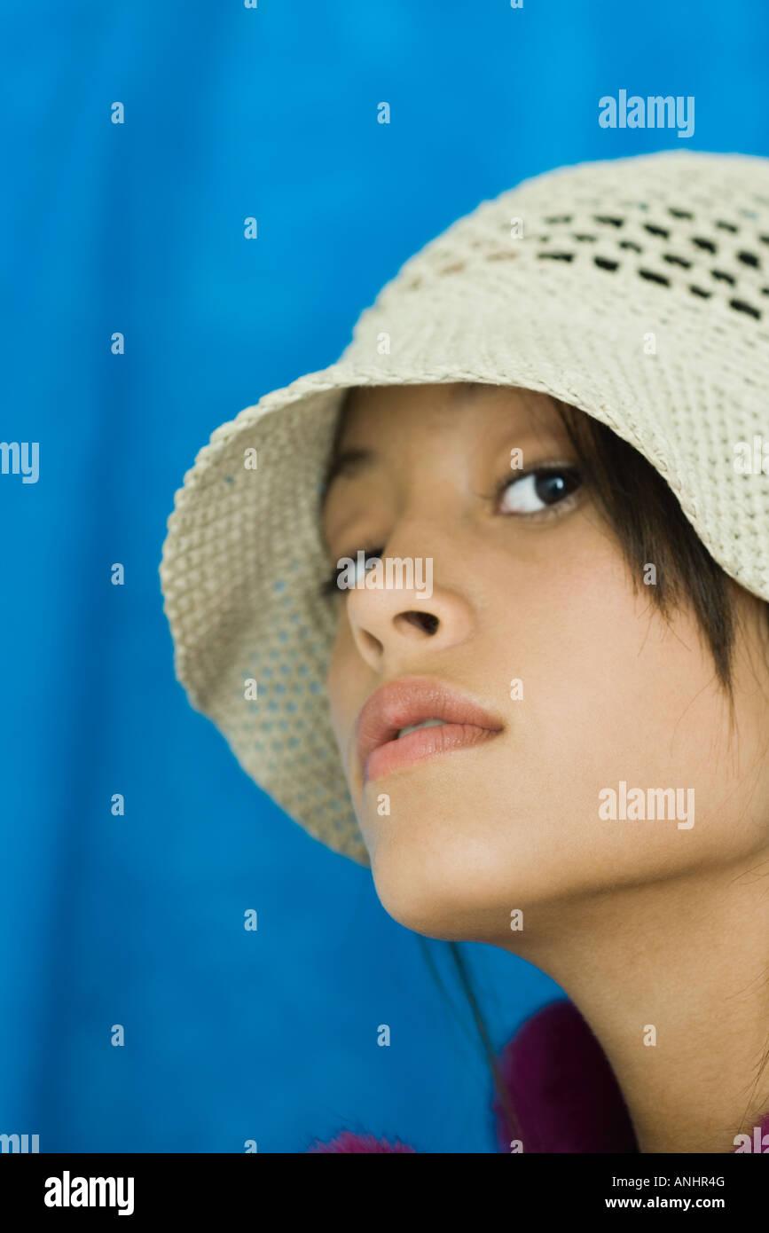 Teenage girl wearing hat, looking at camera, close-up - Stock Image