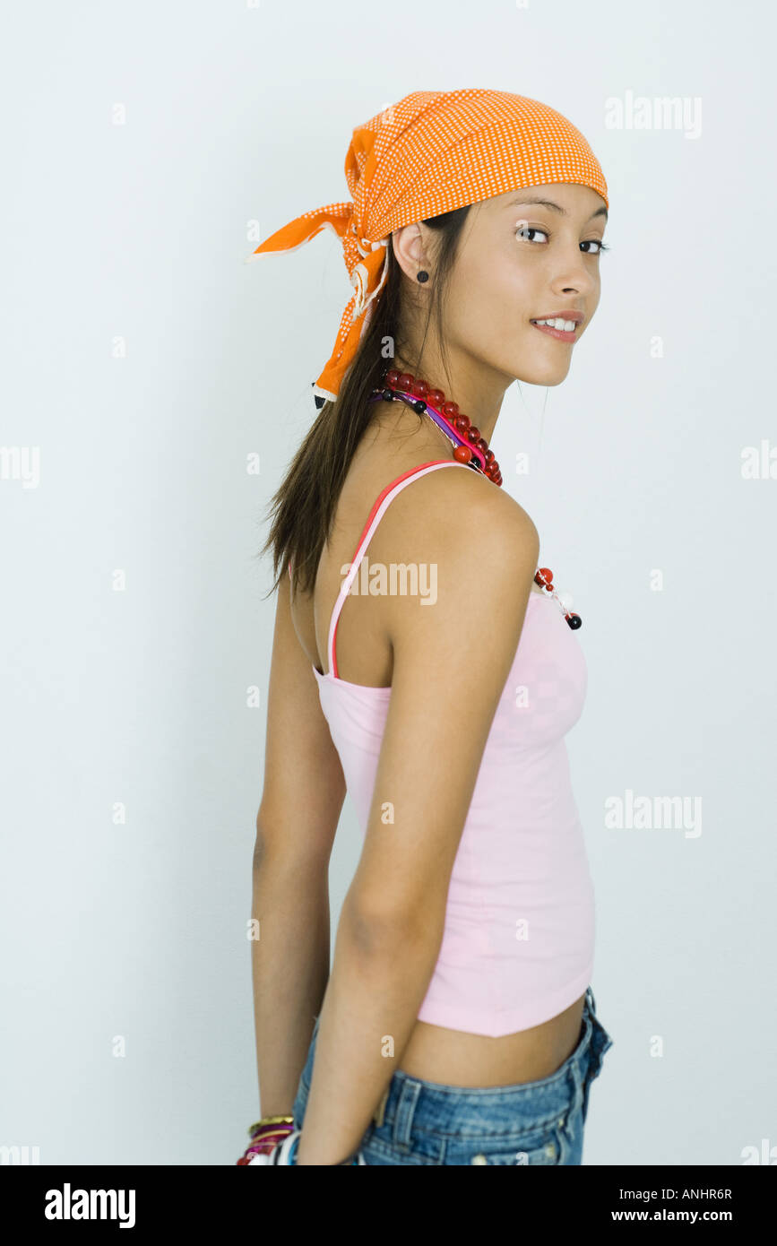 Teenage girl standing with hands behind back, looking over shoulder at camera - Stock Image