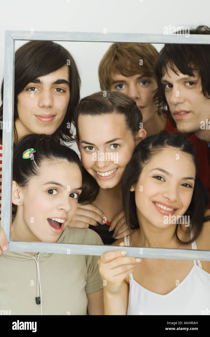 Young friends smiling at camera through picture frame, group portrait - Stock Image