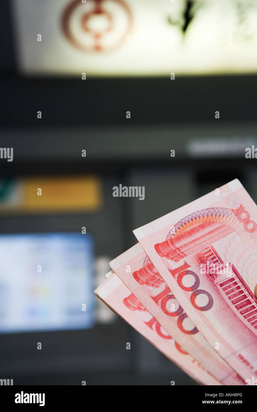 100 Yuan banknotes, AMT in background - Stock Image