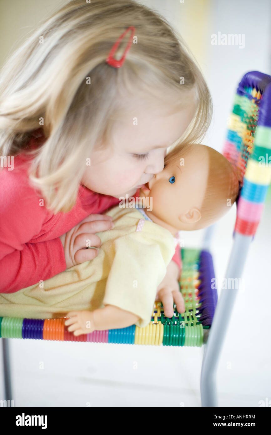Blonde toddler girl kissing baby doll - Stock Image