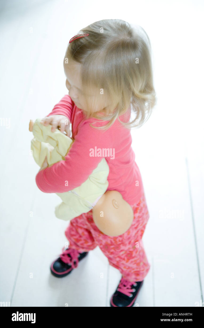 Blonde toddler girl holding baby doll upside down - Stock Image