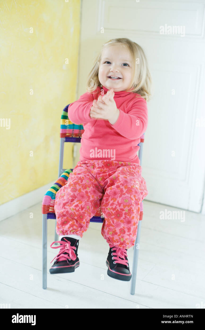 Blonde toddler girl sitting in chair, clapping - Stock Image