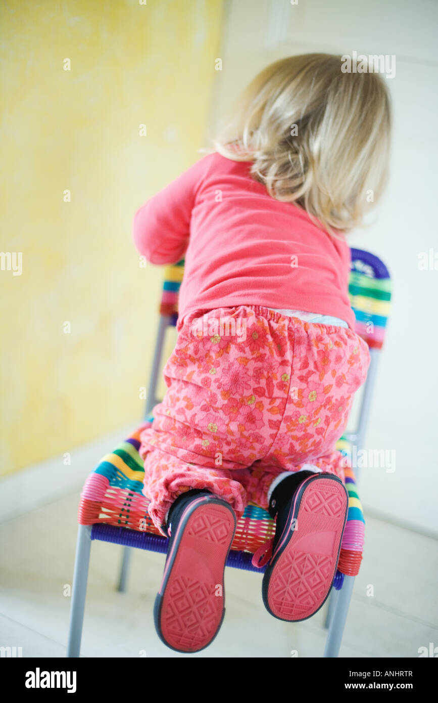 Blonde Toddler Girl Climbing On Chair, Rear View