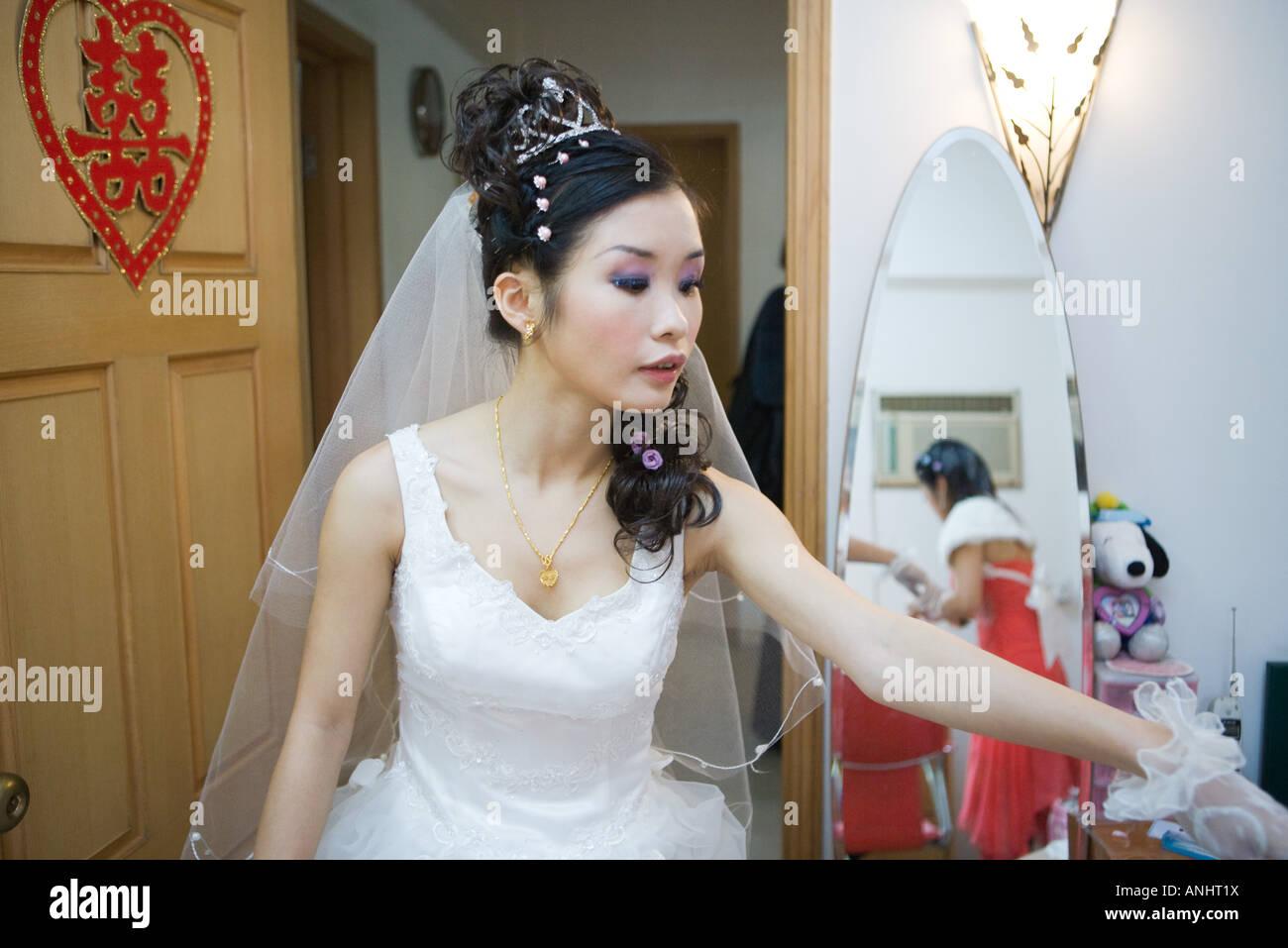 Bride in bedroom, Chinese character on door, looking away Stock Photo