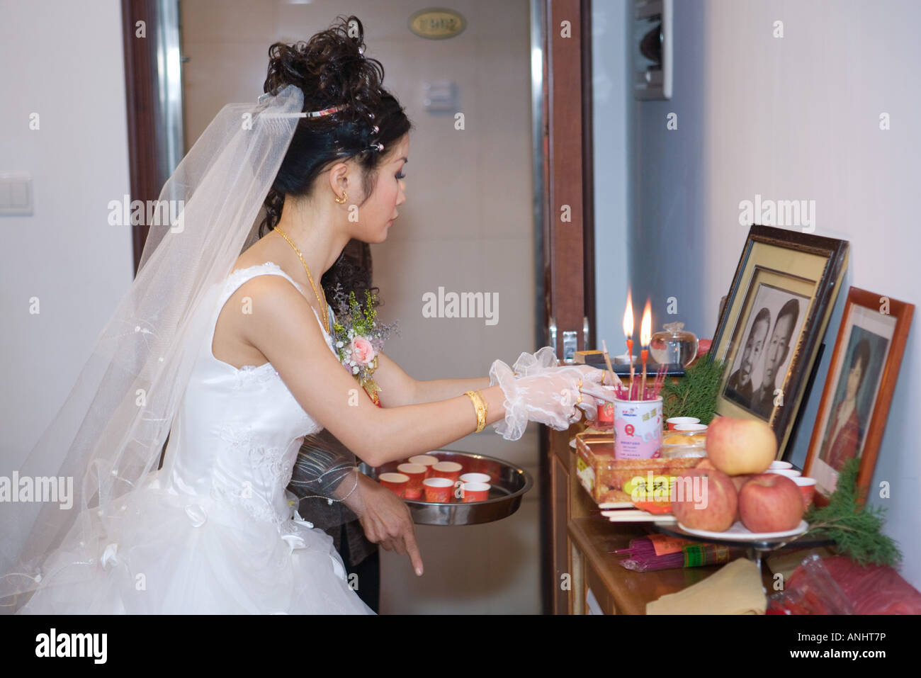Chinese wedding, bride taking offering to ancestral shrine - Stock Image
