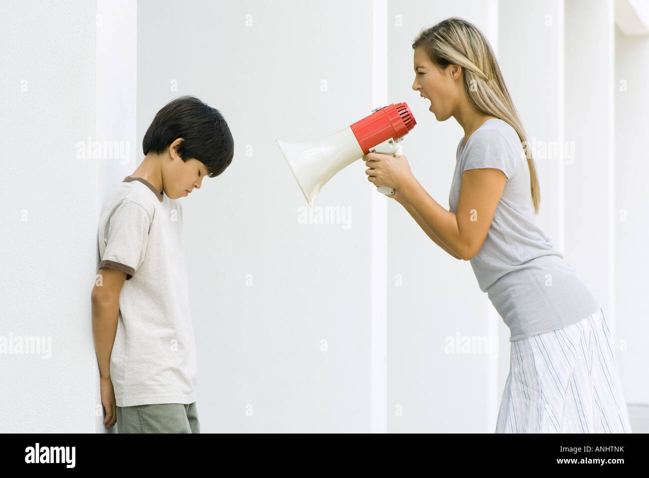 Woman shouting at boy through megaphone - Stock Image