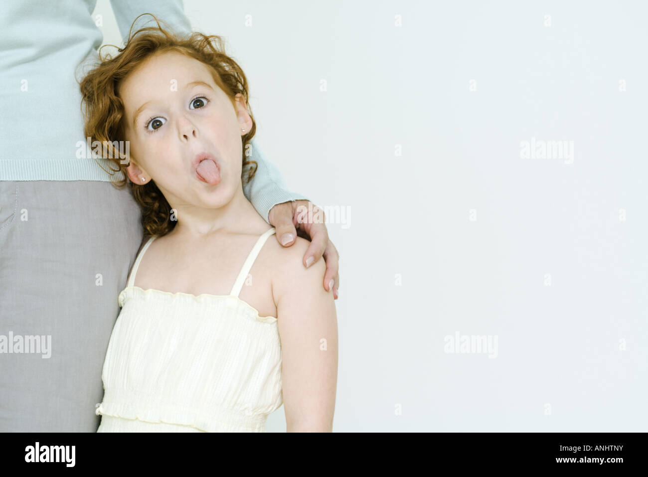 Little girl holding onto mother's leg, sticking tongue out at camera - Stock Image