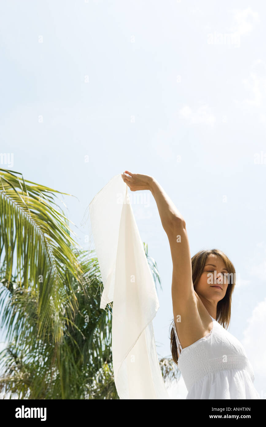 Woman standing in sun in tropical setting, holding up wrap, eyes closed, low angle view - Stock Image