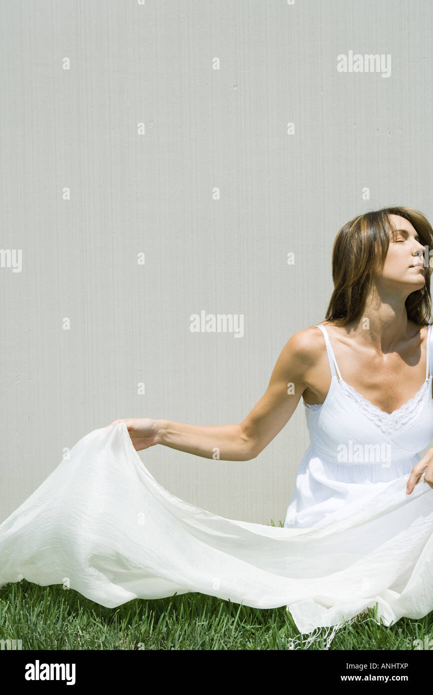 Woman sitting on grass in sun, holding light wrap, eyes closed - Stock Image